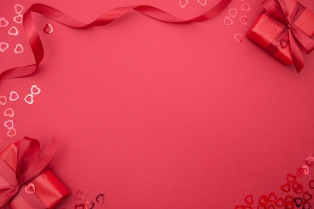 Красные подарочные коробки и ленты луки, красный фон с красным бантом. вид сверху. копировать пространство рождество, вечеринка или день валентина.