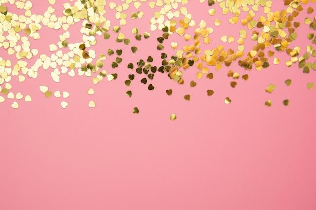 ピンクの背景に抽象的なテクスチャ背景、黄金の心形キラキラ。バレンタインデー、愛、誕生日、パーティーのコンセプト。