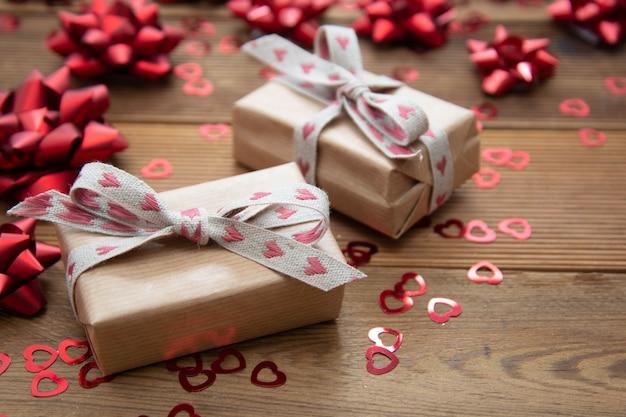 赤い弓と紙吹雪、木製のテーブルの上に茶色のクラフトペーパーギフトボックス。バレンタインデー、誕生日。
