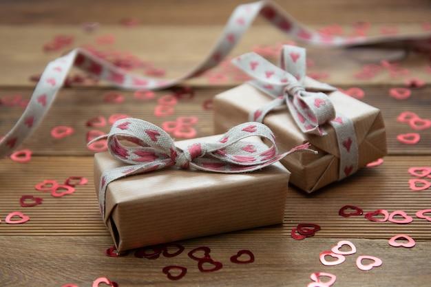 赤い弓と紙吹雪、木製のテーブルの上に茶色のクラフトペーパーギフトボックス。バレンタインの日、誕生日、パーティーのコンセプト。