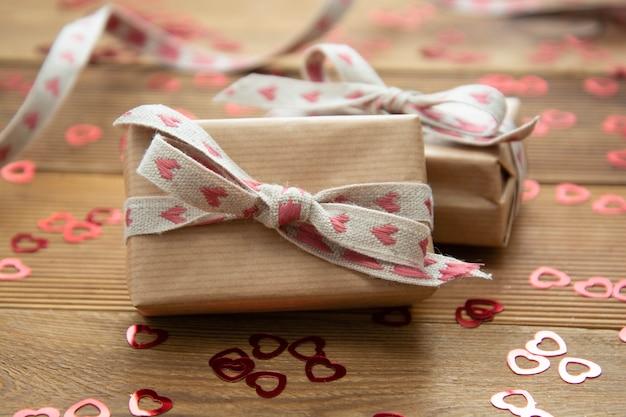 木製のテーブルの上の赤い弓と紙吹雪でクラフト茶色の紙ギフトボックス。バレンタイン・デー
