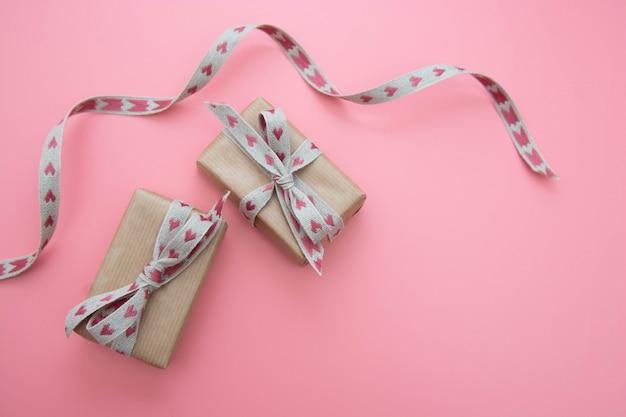 ピンクのクラフト紙と弓に包まれたギフトボックス。バレンタインデー、誕生日。