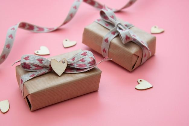 ピンクのクラフト紙と弓に包まれたギフトボックス。バレンタインの日、誕生日、パーティーのコンセプト。