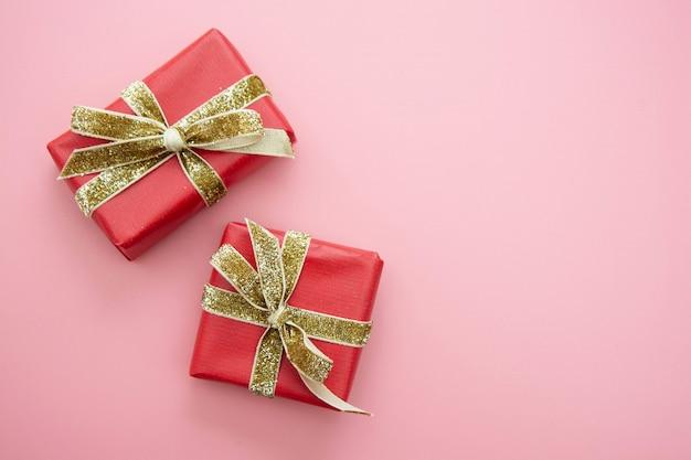 赤いギフトボックスとピンクの背景の黄金の弓。バレンタインの日、誕生日、パーティーのコンセプト。