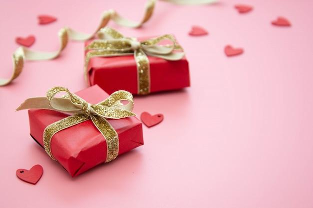 赤いギフトボックスとピンクの黄金の弓。バレンタインの日、誕生日、パーティーのコンセプト。