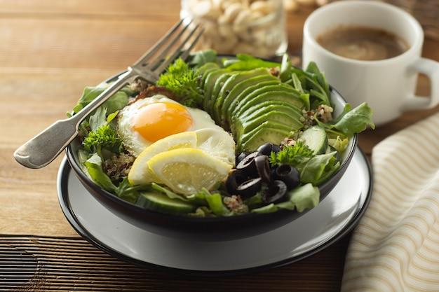 健康食品。卵、キノア、アボカド、グリーンサラダ、ブラックオリーブ。木製のテーブルダイエット、体重を減らす。