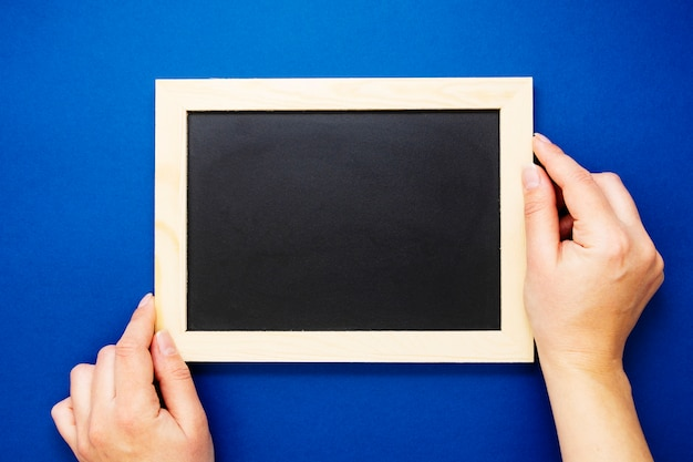 黒板のモックアップ。分離された青色の背景に黒板を保持している女性の手。コピースペース、フラットレイアウト。ビジネス、教育の概念。