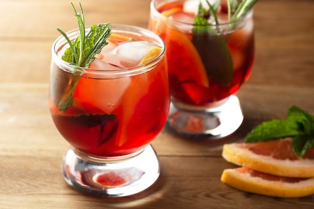 グレープフルーツとローズマリーのジンカクテル、爽やかな夏、冷たいピンクの飲み物。木製のテーブル