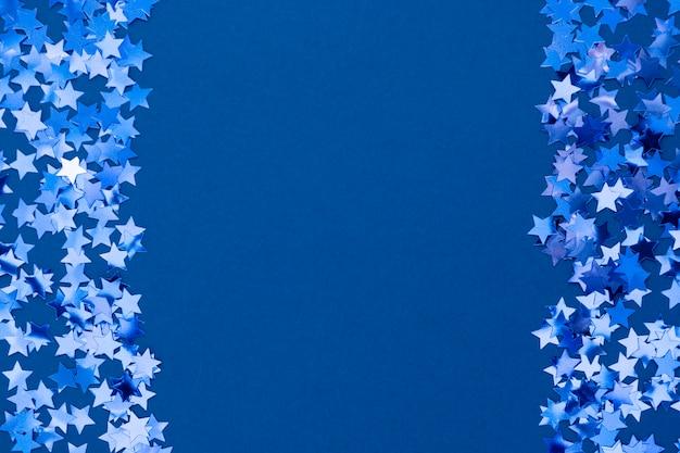 青の抽象的なクリスマス背景の境界線、青の背景に星の紙吹雪とフレームのテクスチャ。テキスト用のスペース。