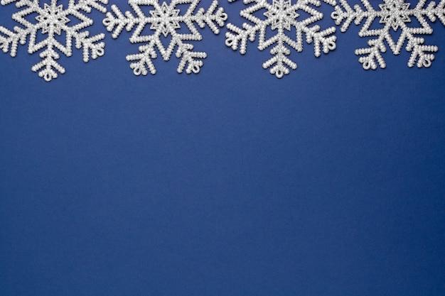銀の雪の冬の装飾、テキスト用のスペースとモックアップブルーブルー抽象的なクリスマス背景。