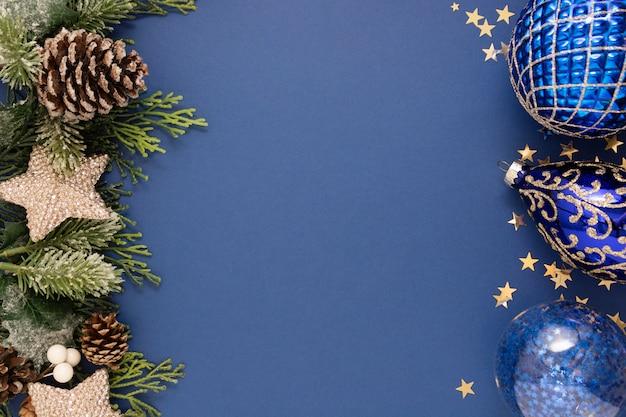青いつまらないと青い背景上のモミの枝とクリスマスブルー抽象的な背景。クリスマスと新年の冬の休日のグリーティングカード。最小限のコンセプト。