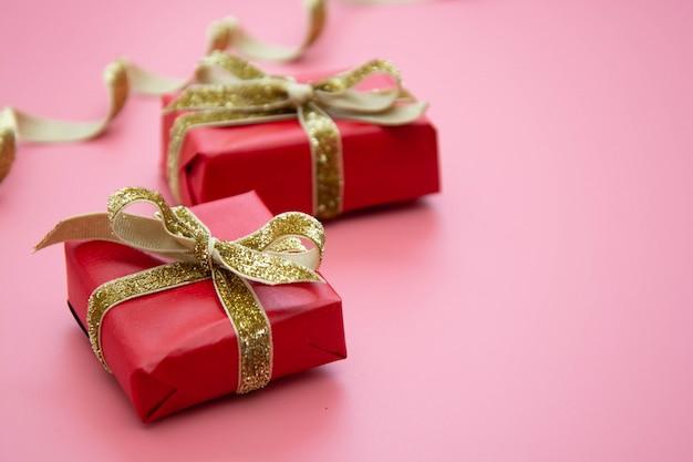 赤いギフトボックスとクリスマスや誕生日の黄金の弓。