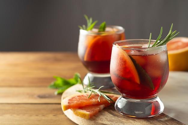 夏の飲み物フルーツのさわやかな冷たいカクテル。木製のテーブル