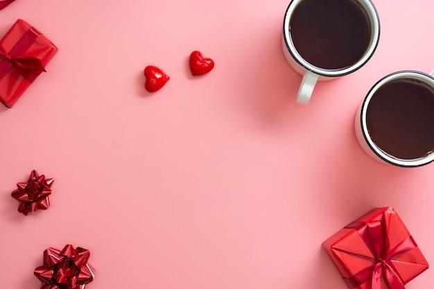 Две чашки и красная подарочная коробка, сердца на розовом фоне, концепция валентина