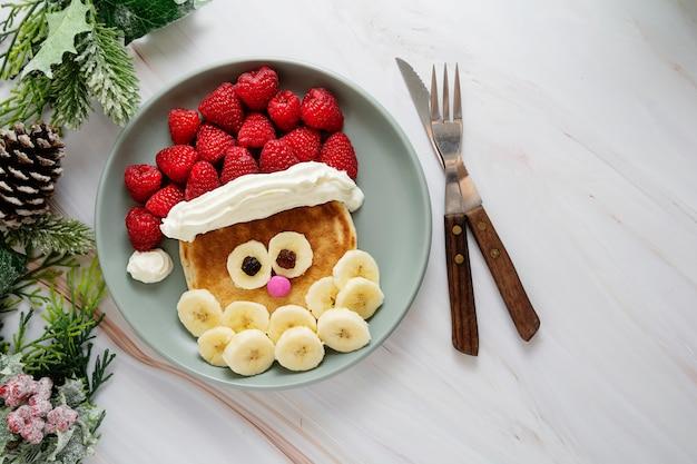 子供のための楽しい食べ物。ラズベリーとバナナのクリスマスサンタパンケーキ。