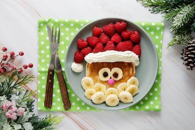クリスマスフード-子供のためのラズベリーとバナナのサンタパンケーキ。