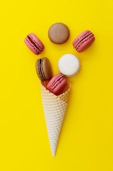黄色の背景にマカロンとアイスクリームワッフルコーン。平干し、デザート。