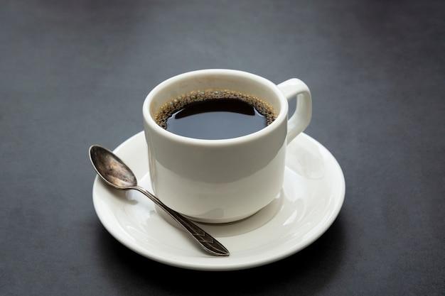 Кофейная чашка изолирована. белая чашка кофе вид сверху ложка и тарелка на темном фоне