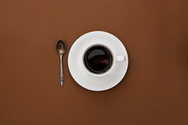 Кофейная чашка изолированная на коричневой таблице. вид сверху, плоский лежал черный кофе напиток с копией пространства.