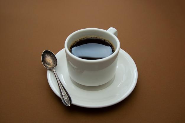 Кофейная чашка изолированная на коричневой таблице. кофейный напиток с копией пространства.