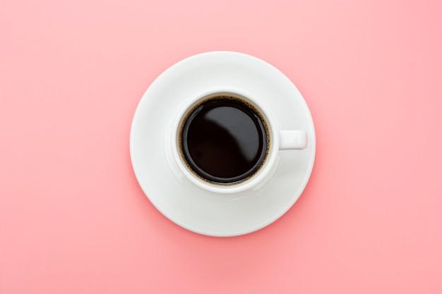 ピンクのテーブルに分離されたコーヒーカップ。平面図、フラットレイアウトの抽象的なブラックコーヒードリンクコピースペース。