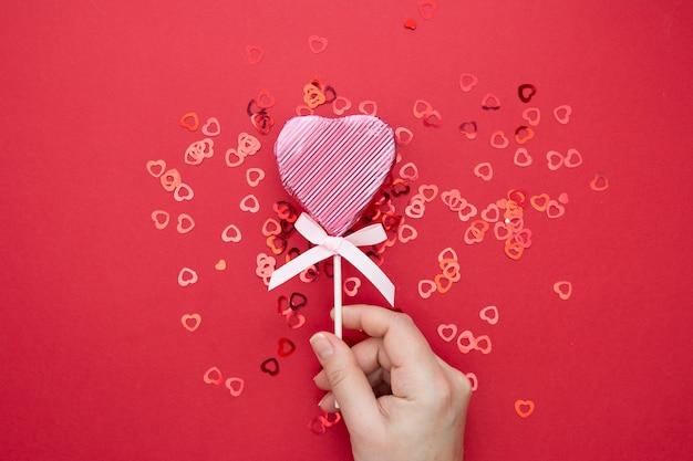 バレンタイン・デー。輝く紙吹雪と赤の背景に分離されたハートの形をしたピンクのロリポップを持っている女性の手。