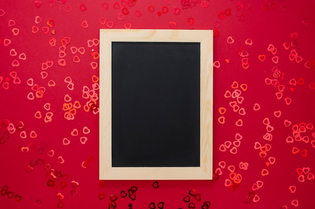 光沢のある紙吹雪と赤い背景の空の黒板の平面図です。