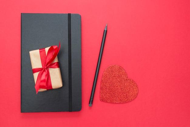 ギフト用の箱と赤の背景に黒のノート。バレンタインデーのコンセプト。