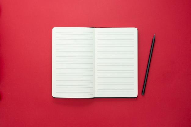 赤い背景に分離されたノートブックを開く、テキスト用のスペースをコピーします。