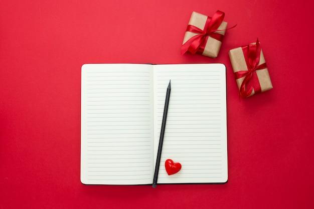 バレンタインデーのモックアップ。赤いハートと赤い背景のギフトボックスでノートブックを開くには、テキスト用のスペースをコピーします。
