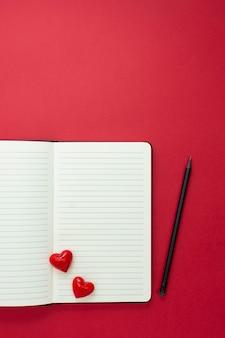 バレンタイン・デー。赤いハートと赤い背景の上の鉛筆でノートブックを開き、テキスト用のスペースをコピーします。
