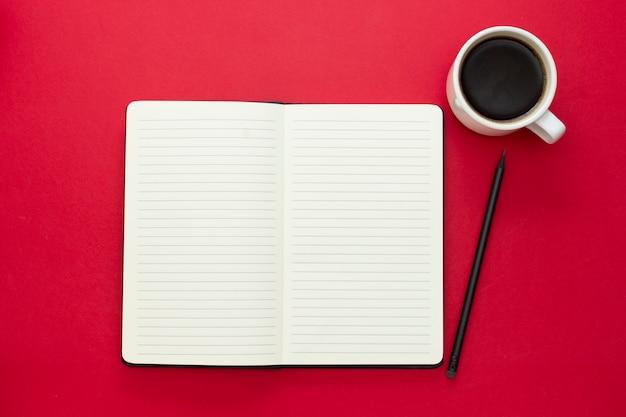 赤の背景にコーヒーカップでノートブックを開きます。