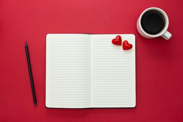День святого валентина. раскройте тетрадь с красными сердцами и карандашем, на красной предпосылке, скопируйте космос для текста.