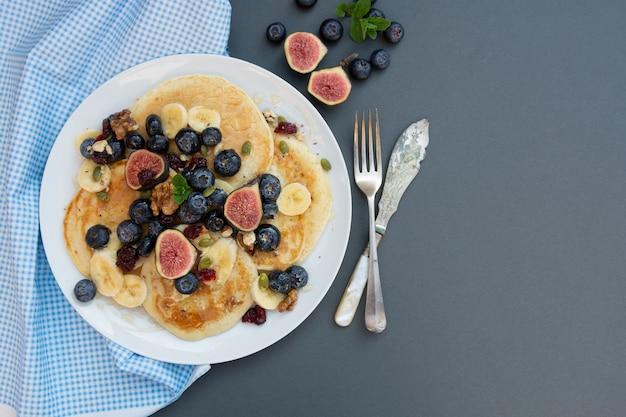 ブルーベリー、ドライフルーツ、蜂蜜のパンケーキ。コーヒーとパンケーキを朝食します。