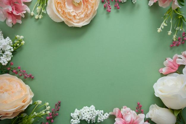緑のボード上の花の組成と春の背景フレーム。お祝いフレームまたは境界線。コピースペースのトップビュー。