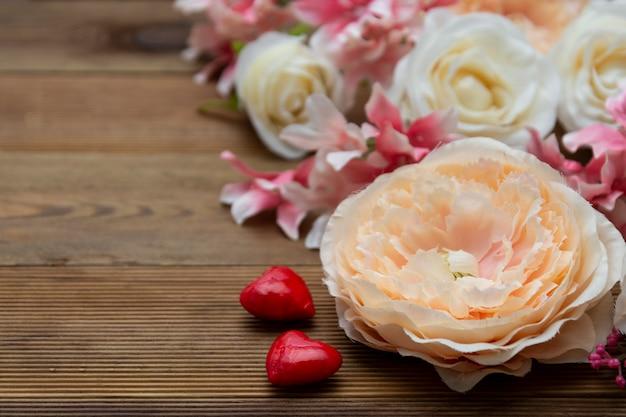 バレンタイン・デー。コピースペースを持つ木製の背景にギフトの花。