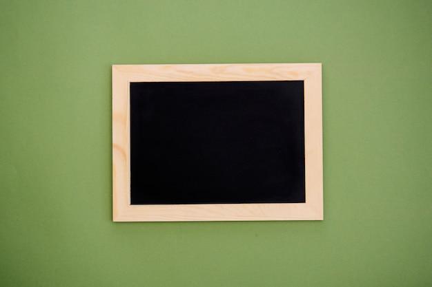 緑の背景に分離された木製フレームで空の黒板。デザインのモックアップ。