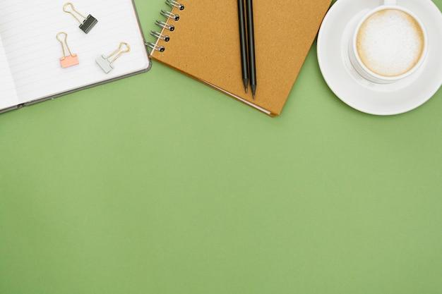 ノートブックとコーヒーカップのオフィスのテーブル。トップタブ、コピースペース付きのワークスペース。創造的なフラットレイアウト。