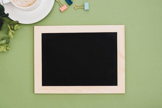 緑の背景の上のコーヒーカップと黒板フレームの平面図です。デザインのモックアップ。コピースペース。