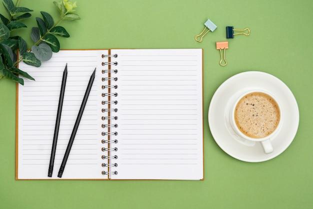 空のページとコーヒーカップでノートブックを開きます。テーブルトップ、緑の背景の作業スペース。創造的なフラットレイアウト。