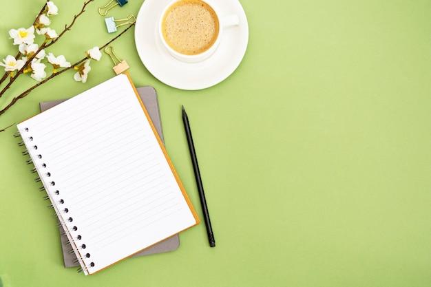 空のページとコーヒーカップでノートブックを開きます。春のテーブルトップ、緑の背景の作業スペース。創造的なフラットレイアウト。