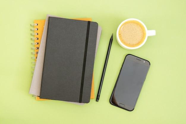 作業テーブルの平面図。黒の閉じたノート、コーヒーカップ、スマートフォン。テキスト用のスペースをコピーします。モックアップの設計。