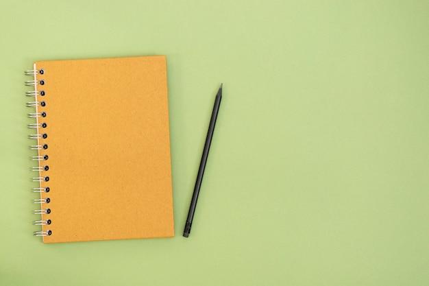 クラフトは閉じたノートとコピースペースを持つ緑の背景の上の鉛筆。モダンでミニマルな作業スペース、ビジネスまたは教育のモックアップ。