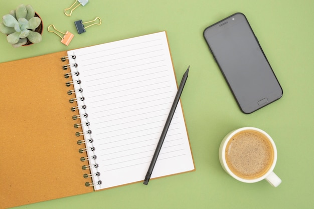 空のページ、コーヒーカップ、鉛筆を持つ手で空白のノートブック。テーブルトップ、緑の背景の作業スペース。創造的なフラットレイアウト。