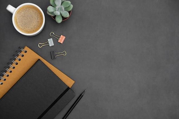 ノートブック、コーヒーカップ、暗いテクスチャ背景の上の緑の多肉植物とモダンでミニマルなテーブルトップ。テキストのコピースペースを持つオフィスまたはビジネスの仕事用スペース。創造的なフラットレイアウト。