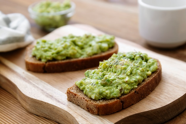 健康食品。木製のまな板にアボカドパスタ、グアコモールとライ麦パン。朝食にアボカドトースト。