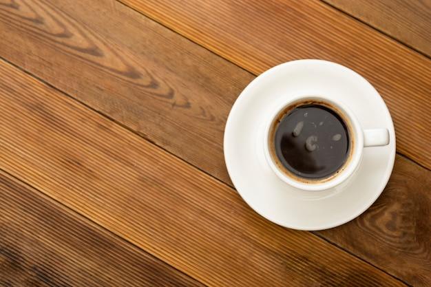 Кофейная чашка изолированная на деревянном столе. вид сверху, плоский лежал кофе напиток с копией пространства.