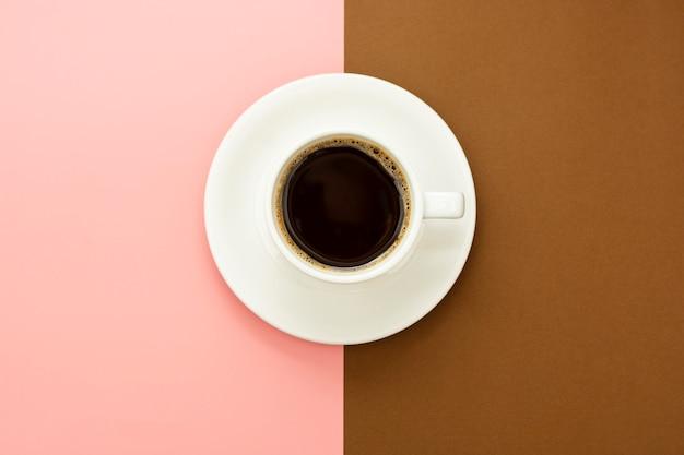 茶色とピンクのテーブルに分離されたコーヒーカップ。フラットレイアウトの抽象的なブラックコーヒー
