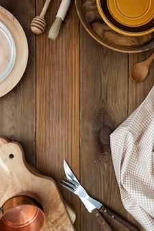 フォーク、ナイフ、木製のテーブルにまな板と木製の丸皿。スペース、メニュー、レシピまたはダイエットの概念をコピーします。