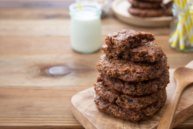 オート麦フレーク、ドライフルーツ、種子を使った健康的な自家製クッキー。木製の素朴なテーブル。